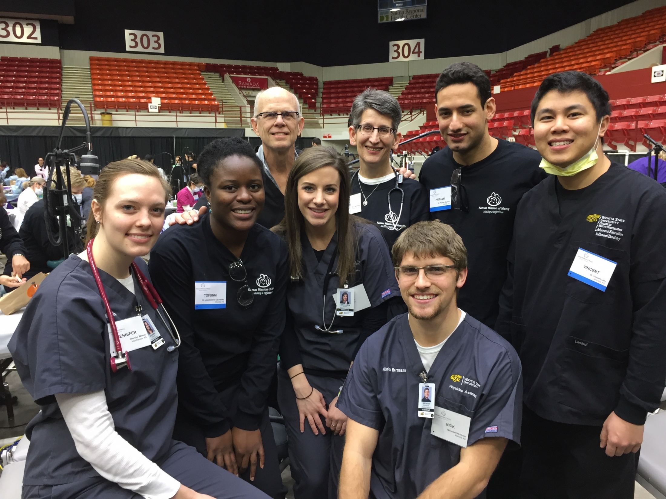 Dental Hygiene and Physician Assistant students are posing for a group picture during the technology fair at Koch Arena. Faculty advisors are also in the picture. All are wearing clinic scrubs.