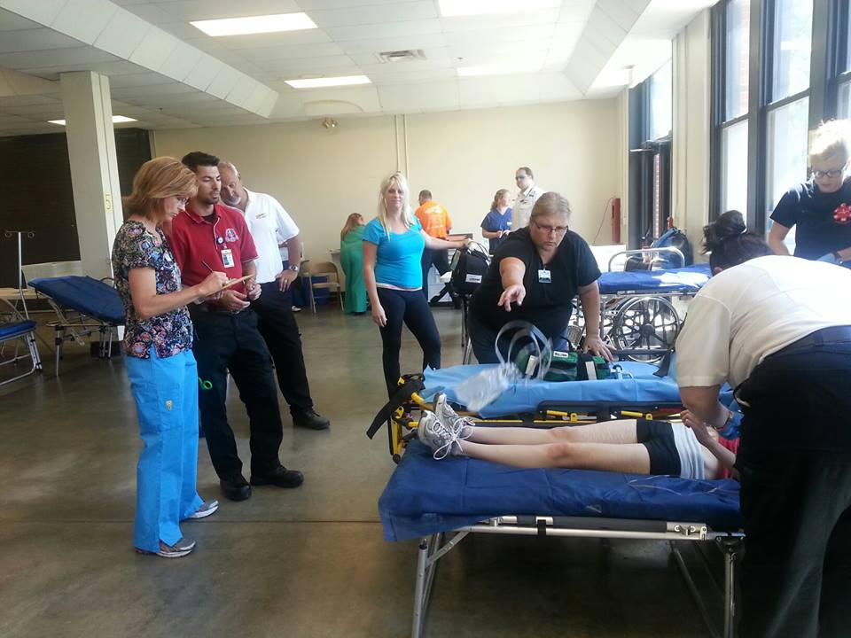Students and faculty advisors participate in an emergency field operations activity. A student is acting as a patient and lying on a cot. They are providing an assessment of the patient.