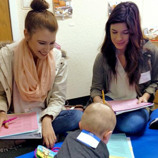 Two students engage with an infant during Baby Days, an event to provide services to children. Both students are holding notebooks with assessment information and the child is playing with a toy.