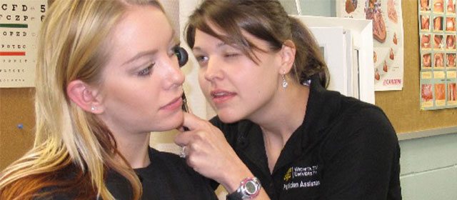 a female student looks inside the ear of a female student patient